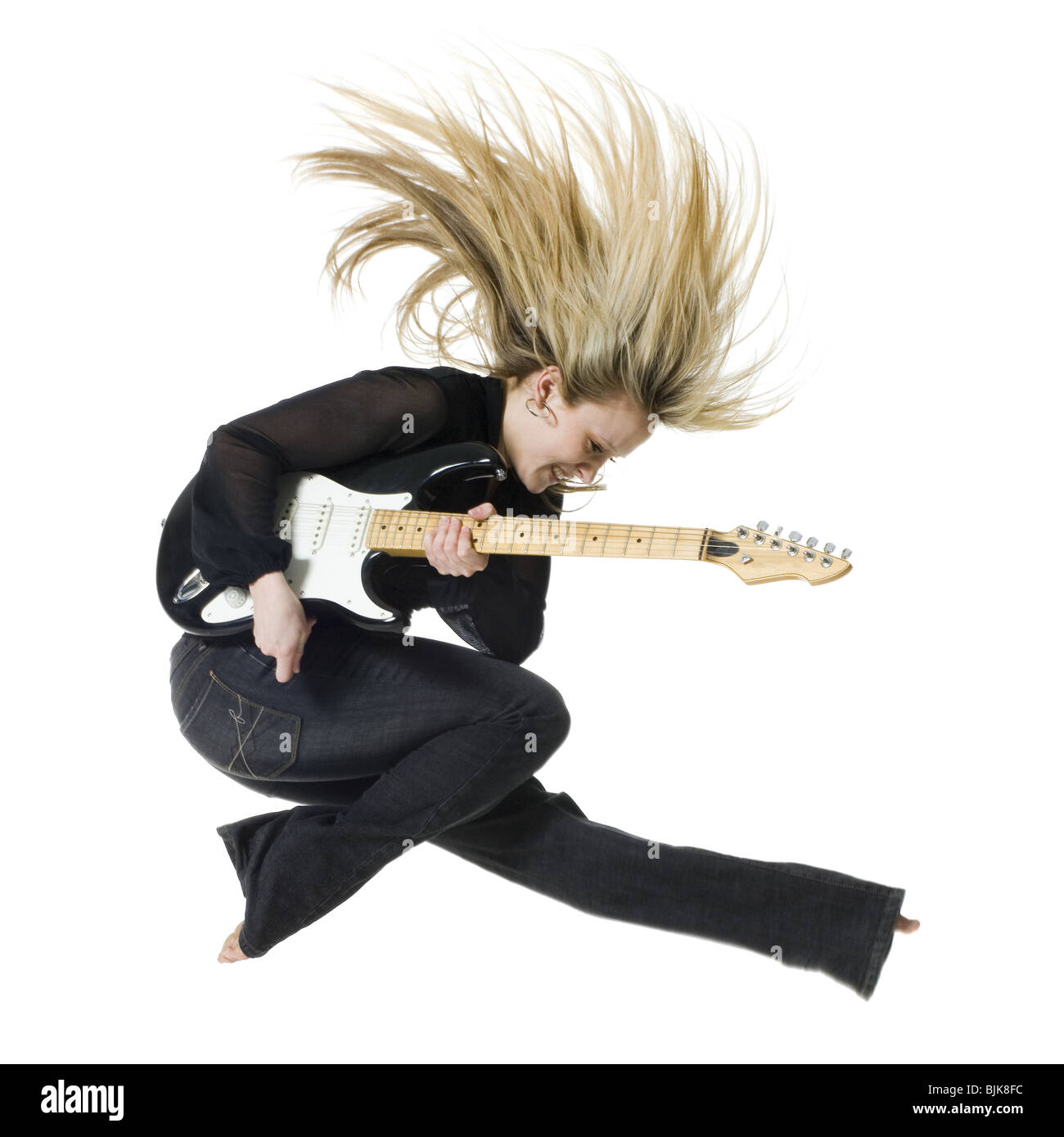 Profile of woman jumping with electric guitar - Stock Image