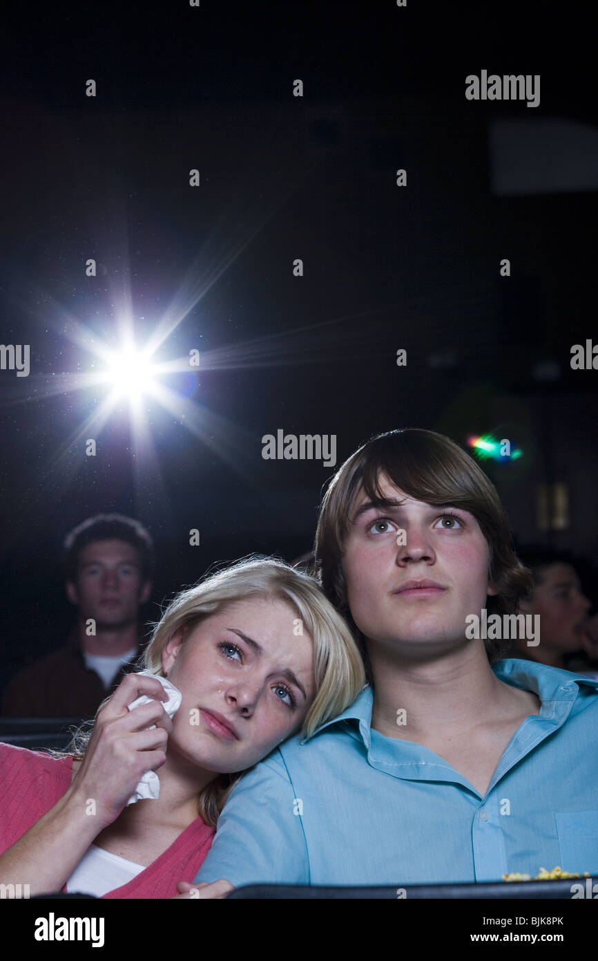 Crying girl and smiling boy watching movie at theater - Stock Image