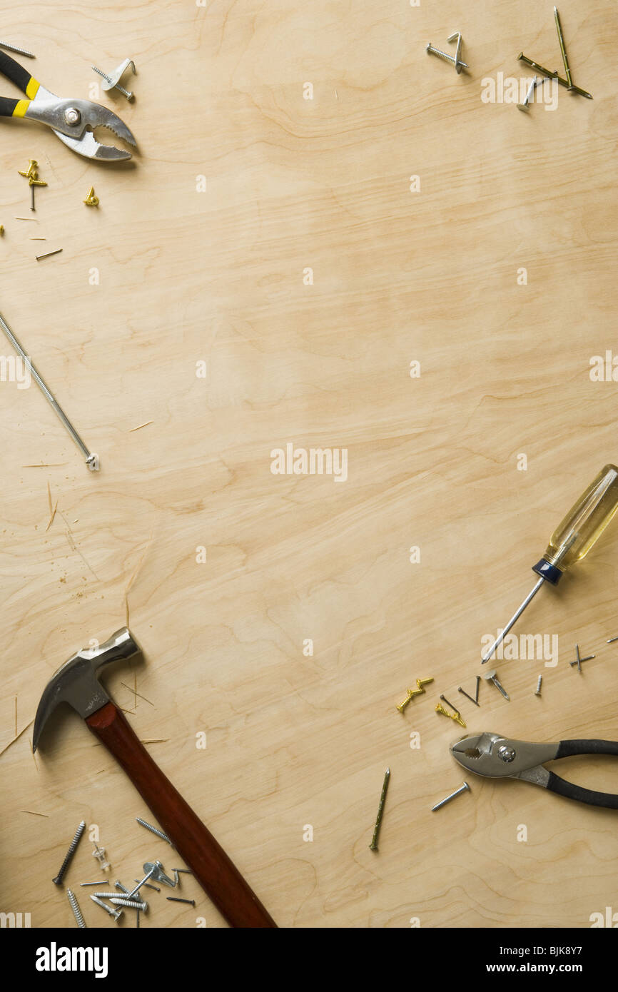 Tools and fasteners on hardwood floor - Stock Image