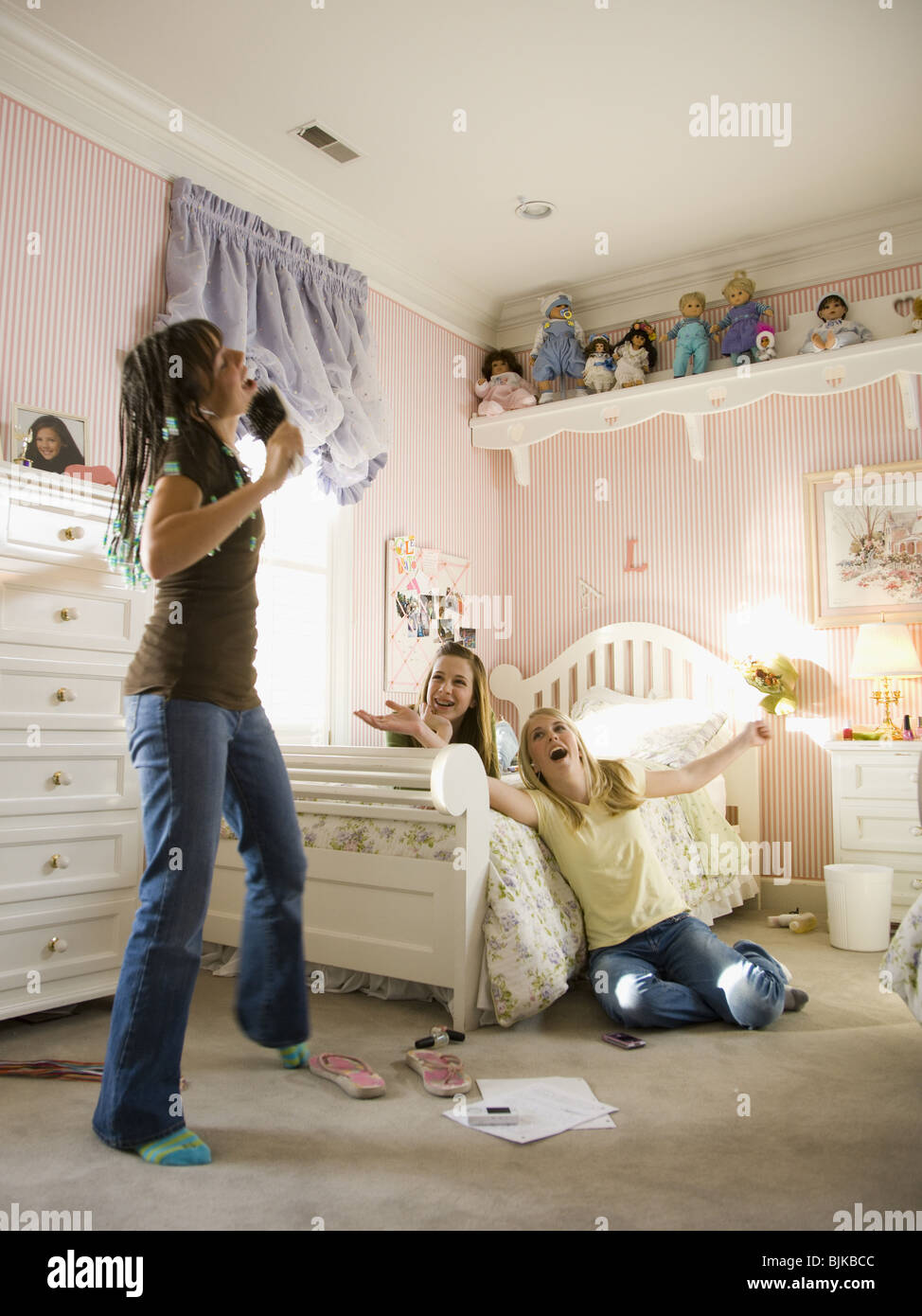 Girl Singing Into Hairbrush In Bedroom With Girlfriends Laughing Stock Photo Alamy
