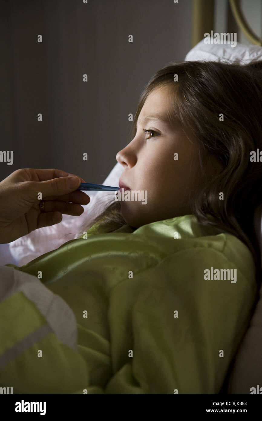 Girl in bed with thermometer - Stock Image