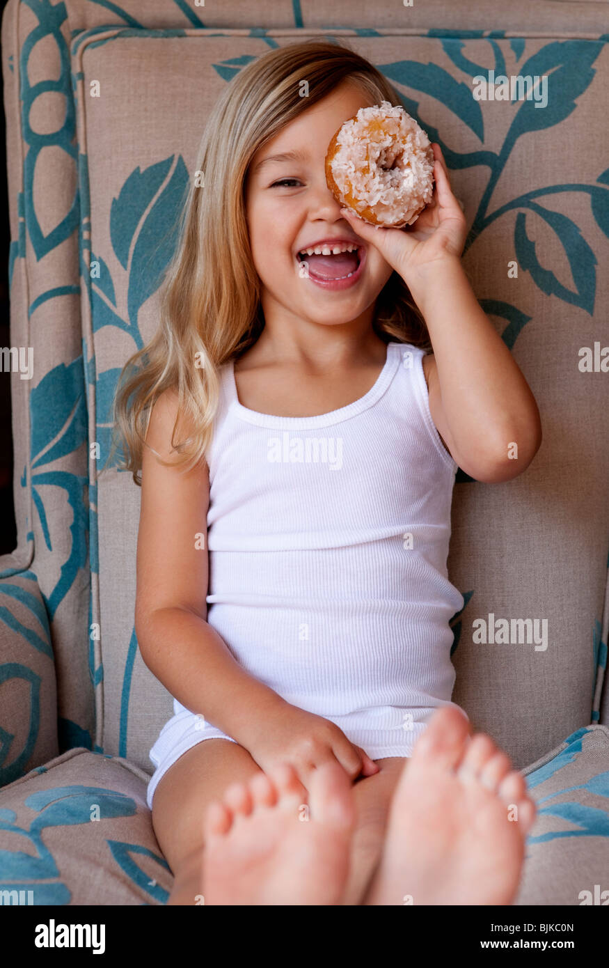 Young girl sitting on chair peeking through donut - Stock Image