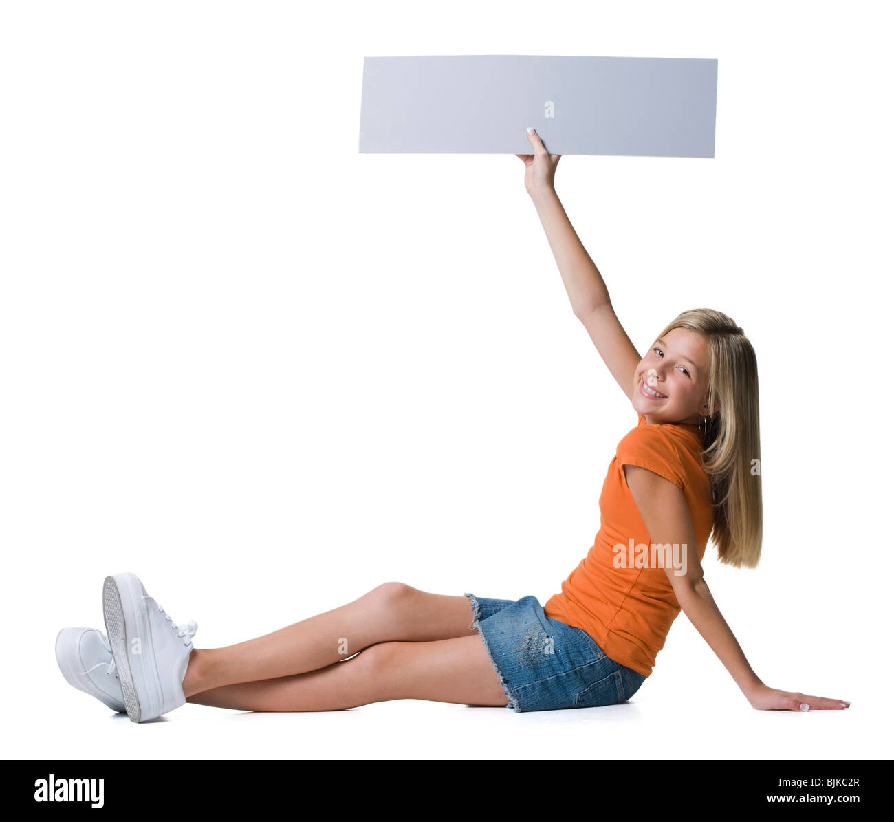 Girl holding blank sign sitting and smiling - Stock Image