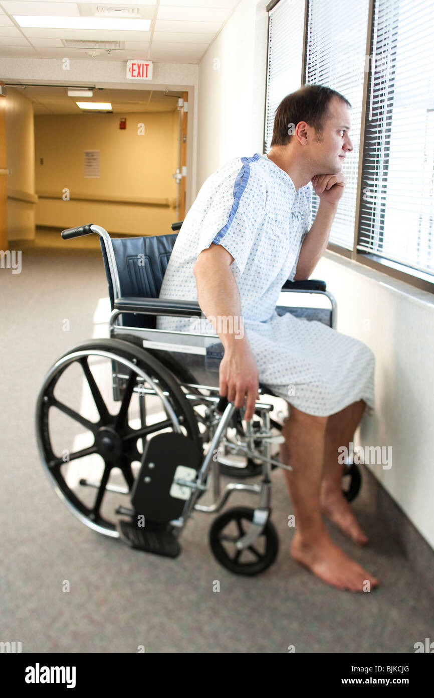 Man in hospital gown sitting in wheelchair looking through window ...