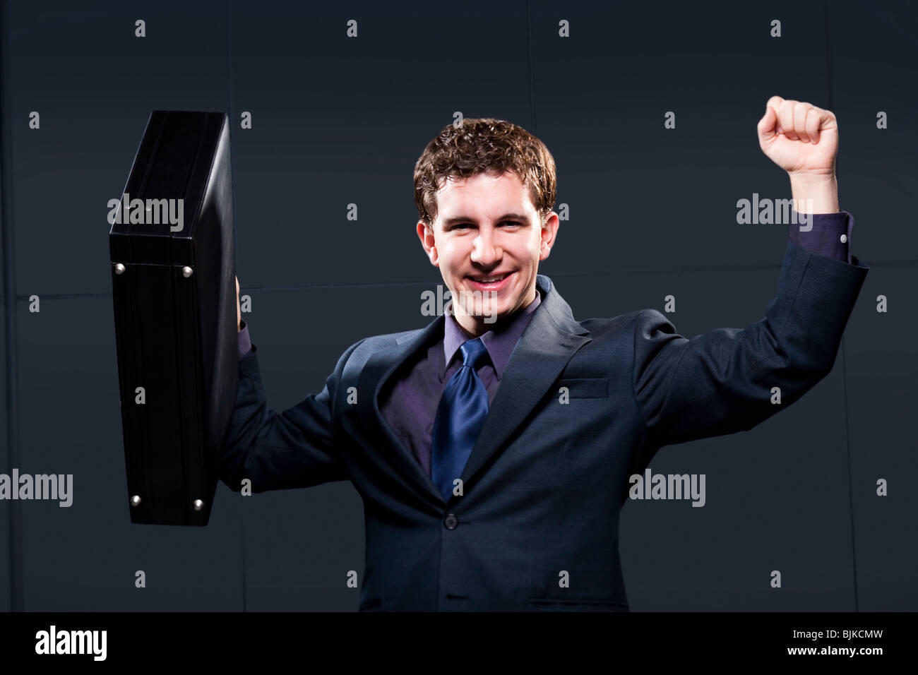 Business man with briefcase and arms up smiling - Stock Image