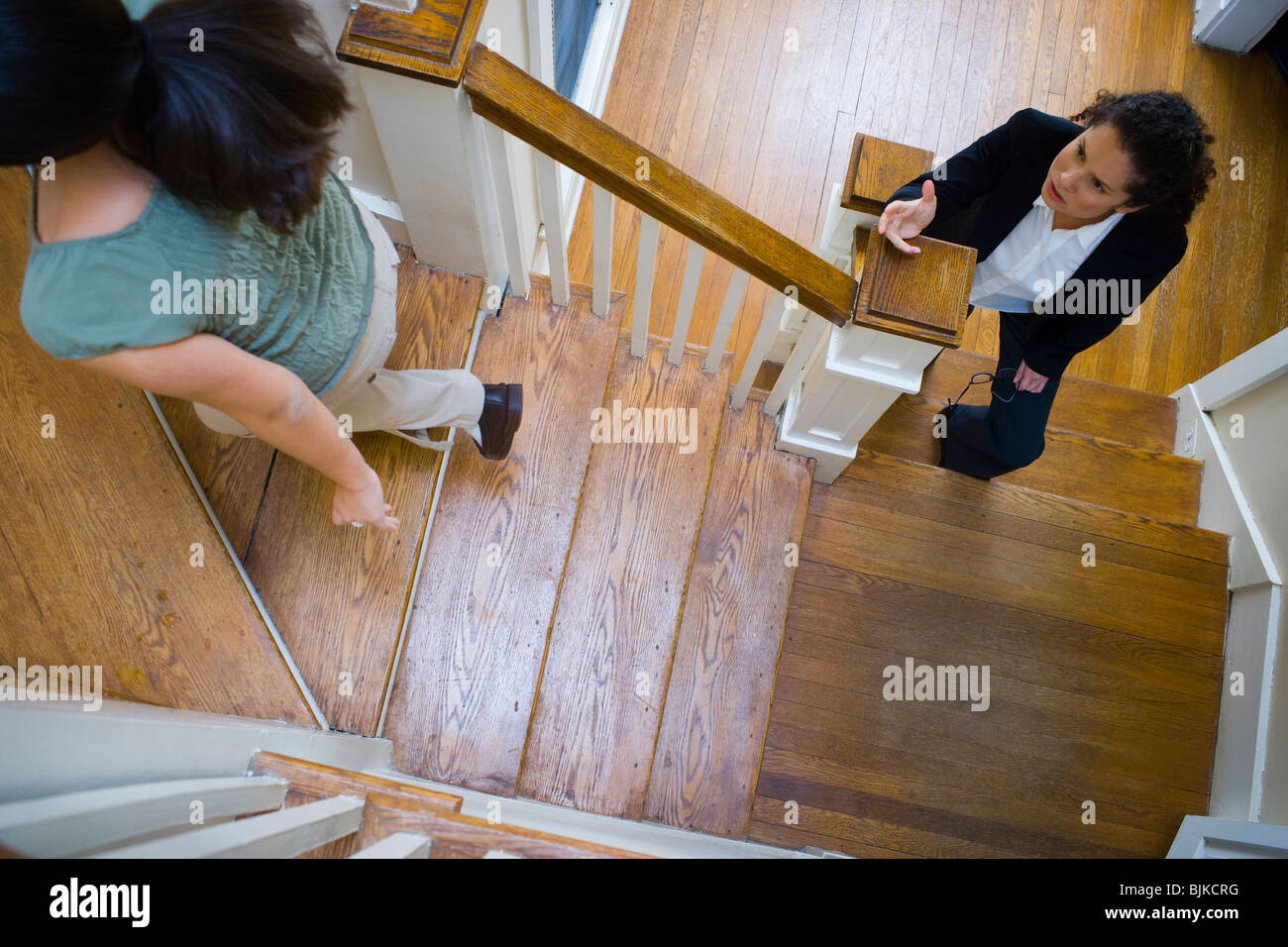 Two women arguing on staircase - Stock Image