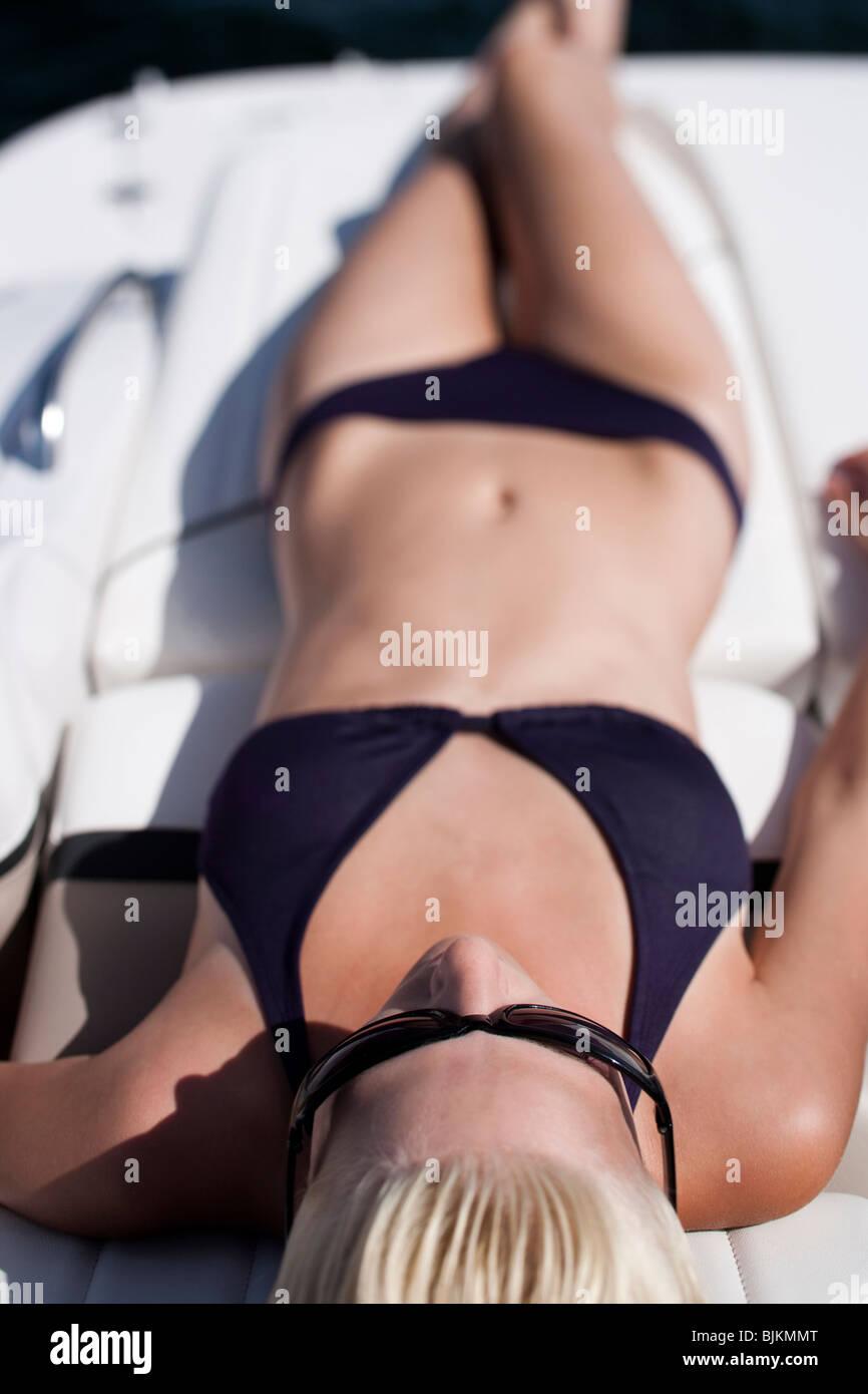 Woman in bikini sunbathing on boat - Stock Image