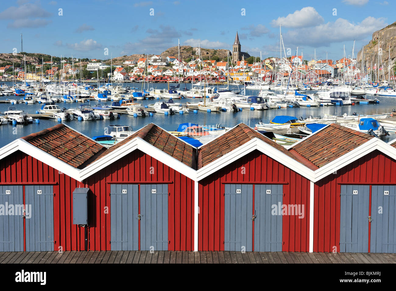 A row of red storage buildings at a marina with boats and a waterfront village seen in the background. Horizontal - Stock Image