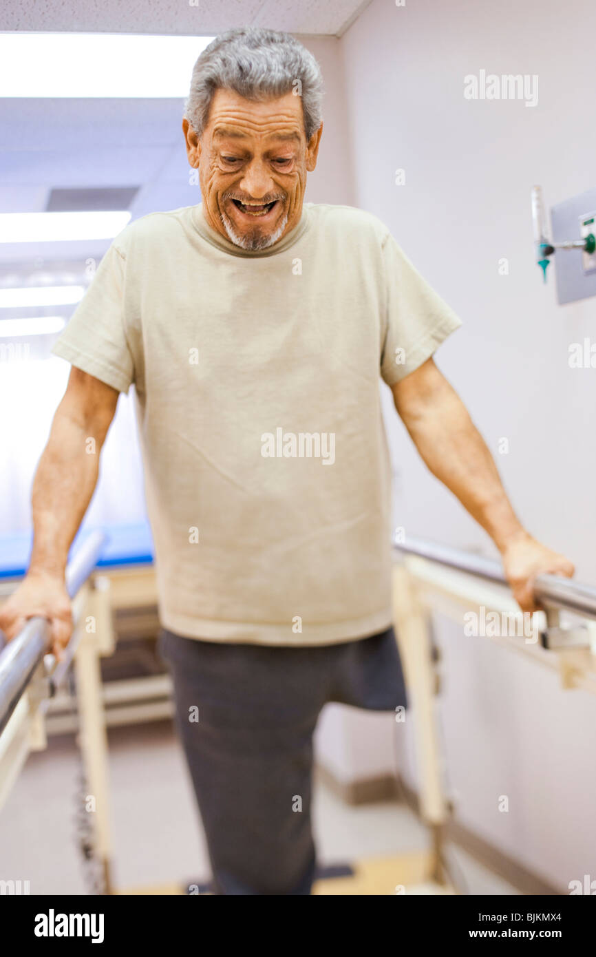 Older man with one leg exercising and smiling - Stock Image