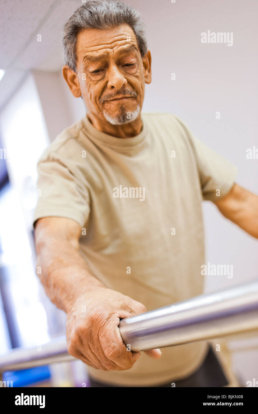 Physical Therapist assisting an older man with one leg in walking - Stock Image