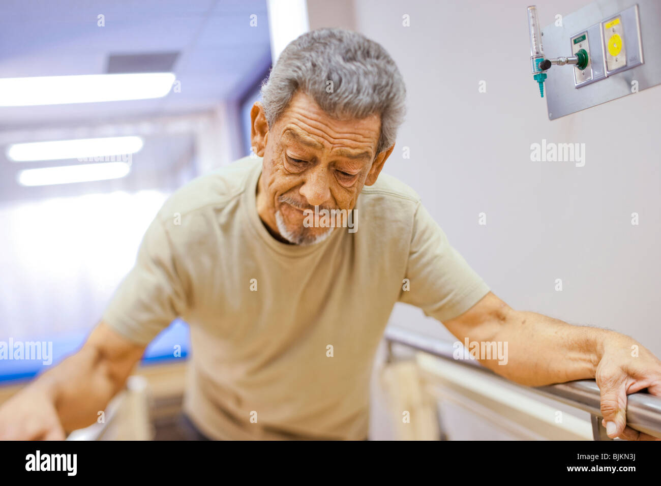 Older man walking with assistance in therapy - Stock Image