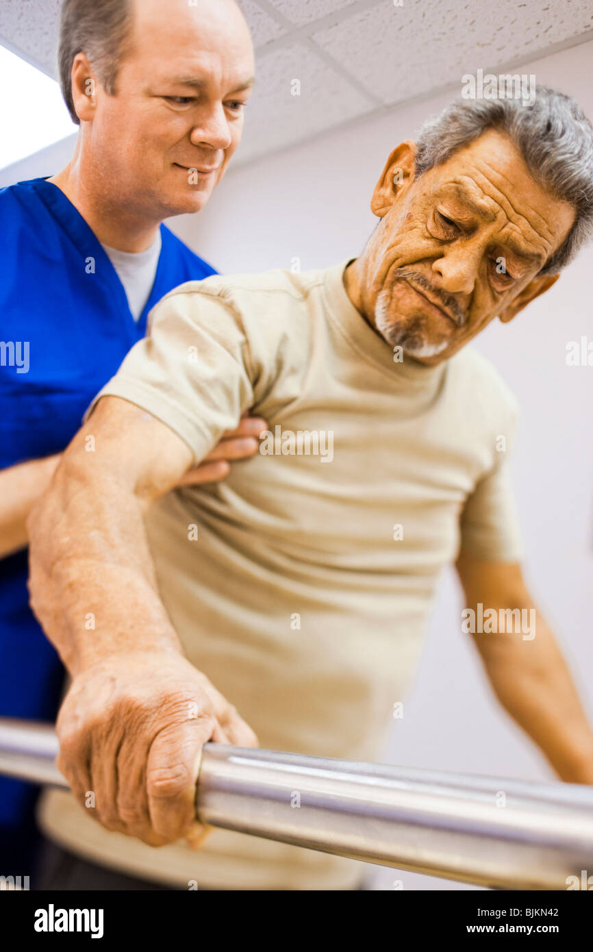 Physical Therapist holding a patient while walking - Stock Image