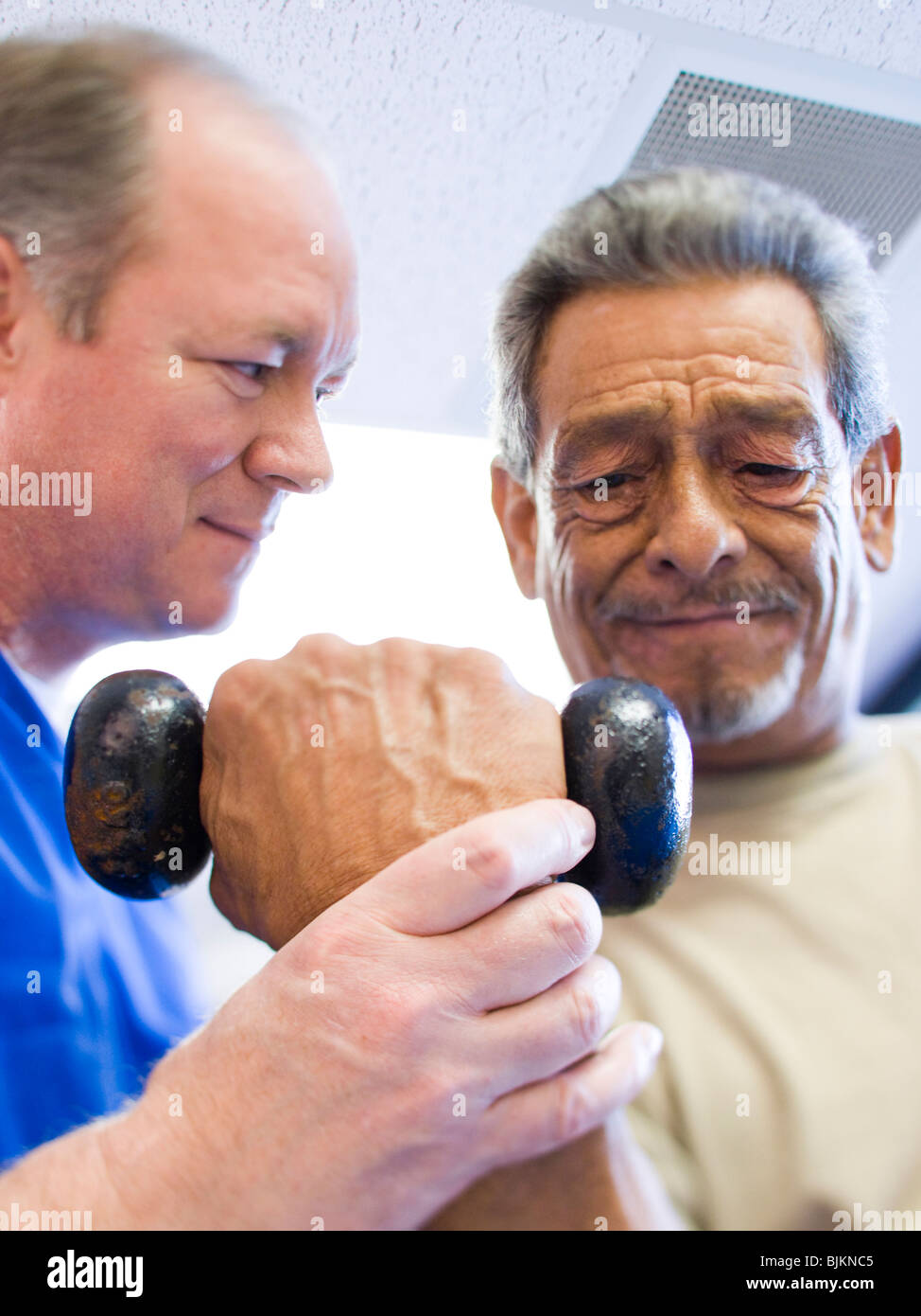 Physical Therapist assisting a man with weights - Stock Image