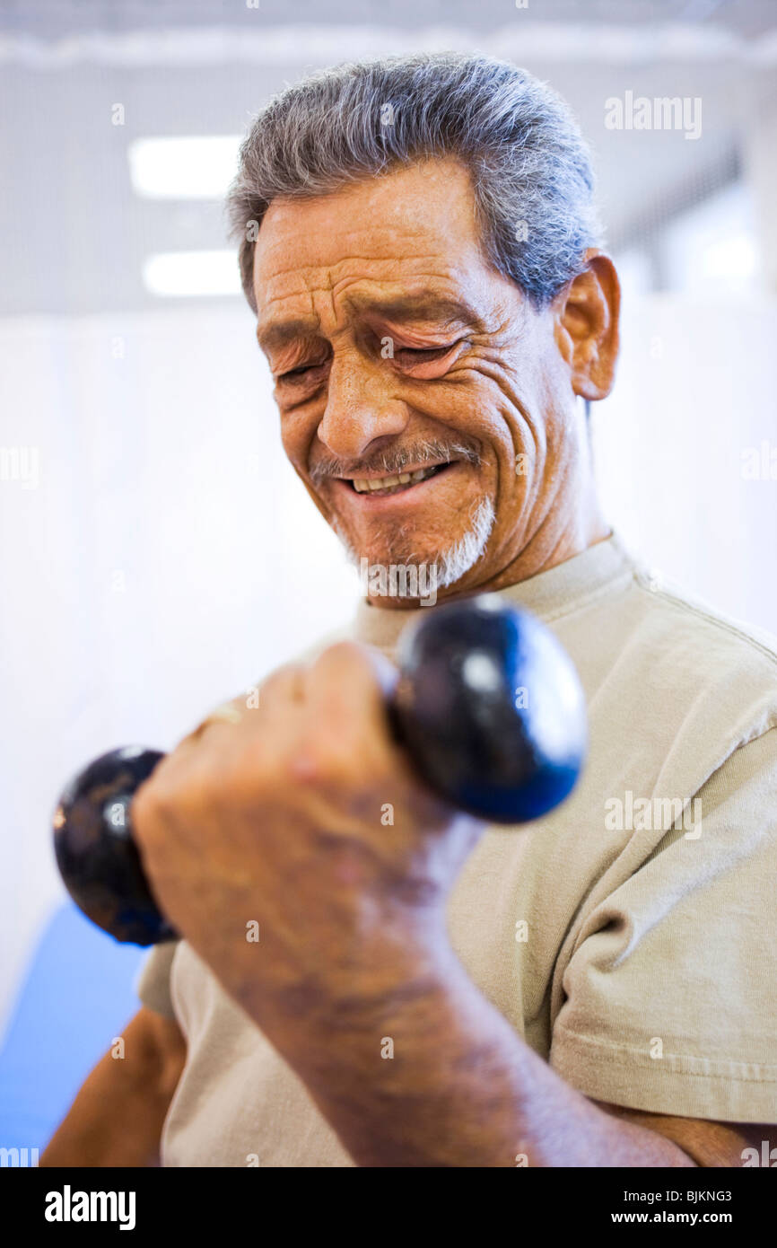 Man with one leg sitting and exercising with weights - Stock Image
