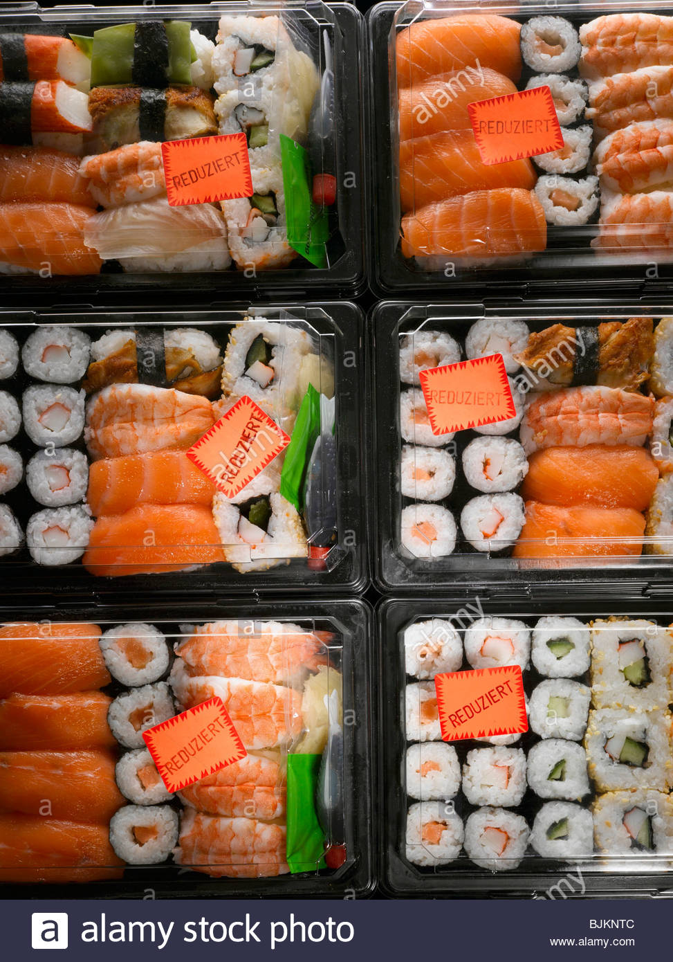 Sushi in plastic boxes with 'Reduced' labels - Stock Image