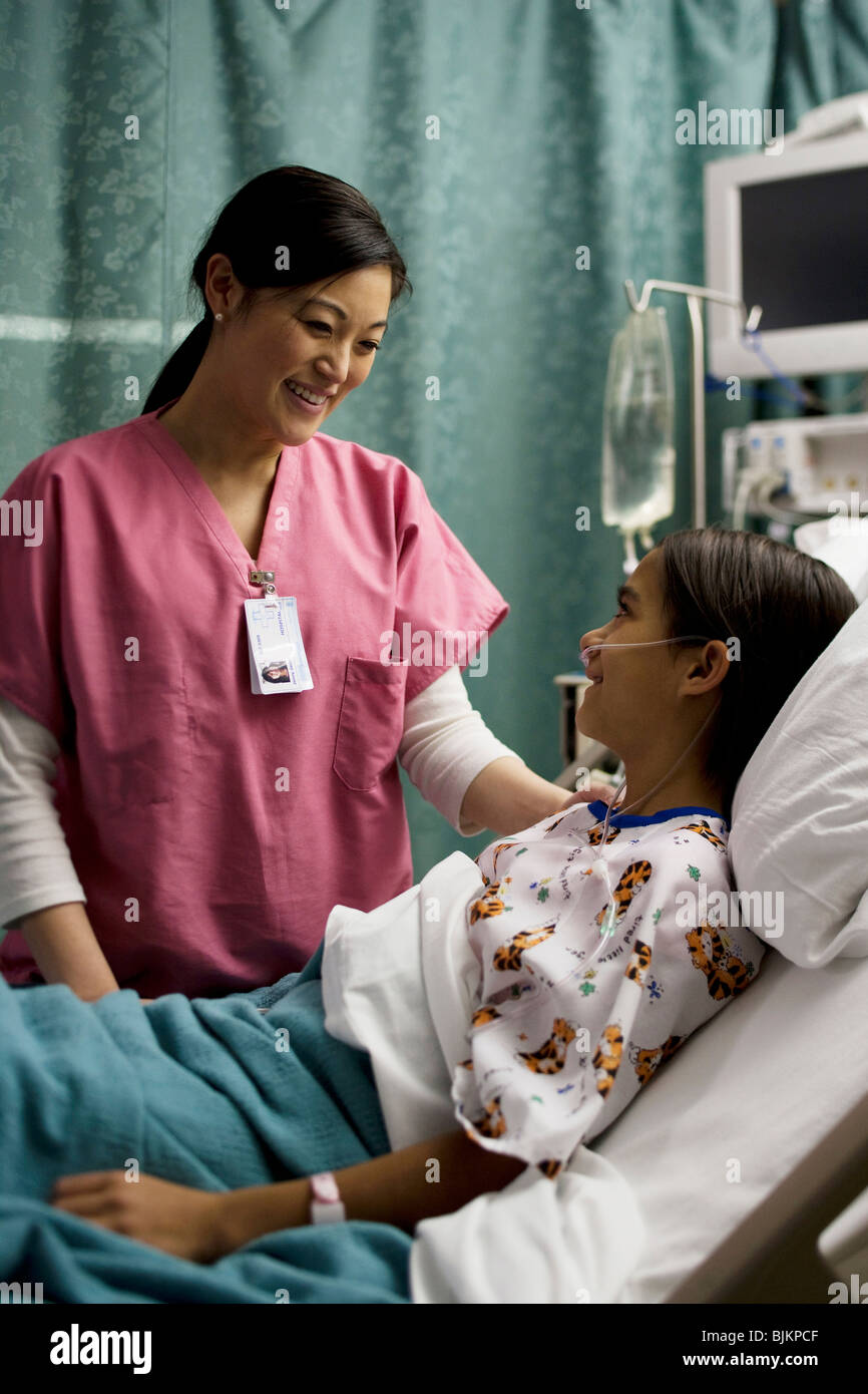 Nurse talking to girl in hospital bed - Stock Image