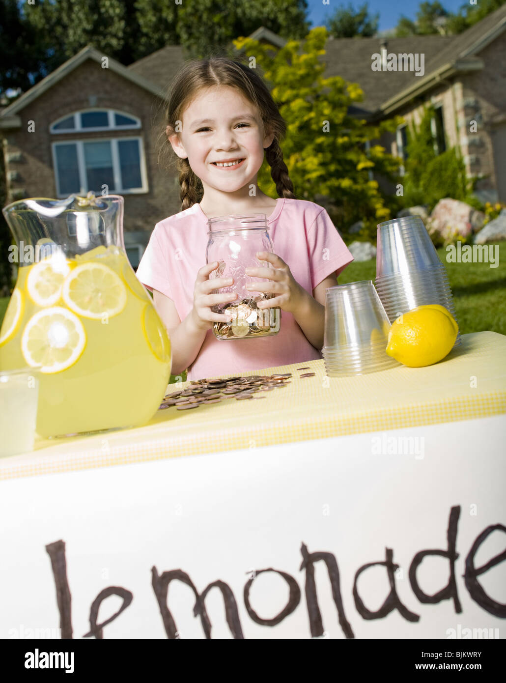Young girl with lemonade stand and money jar - Stock Image