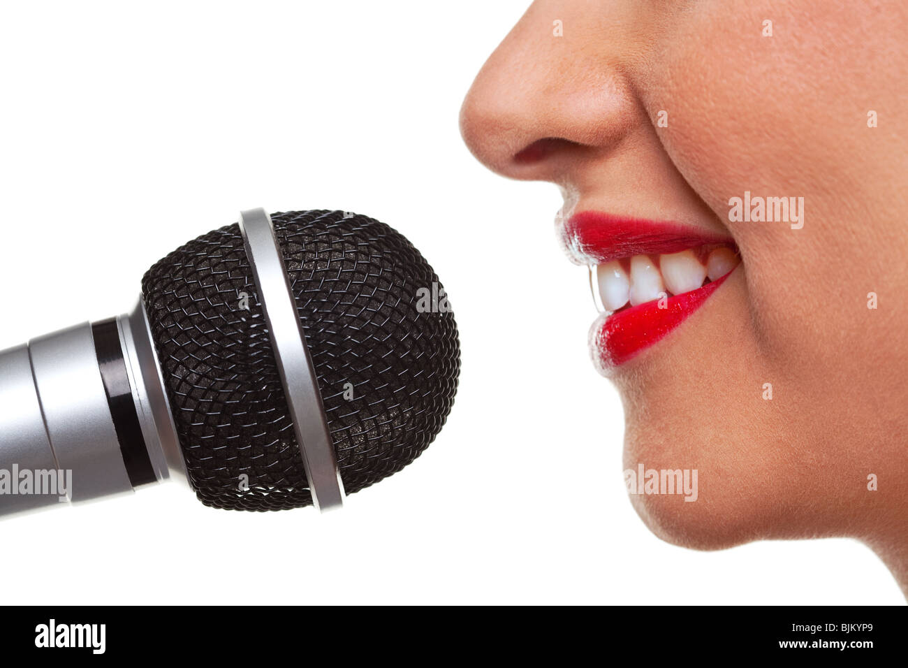 Close up of a woman using a microphone, isolated on a white background. - Stock Image