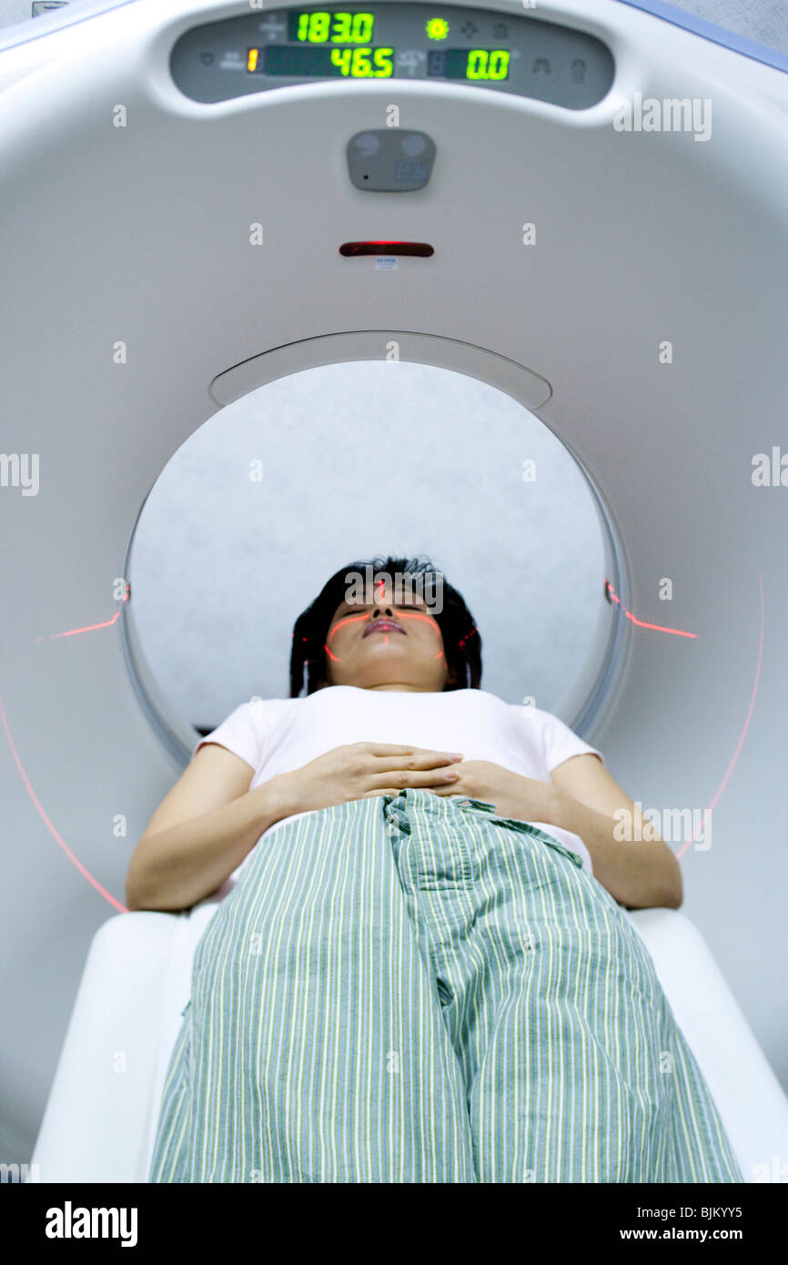 Woman entering MRI machine - Stock Image