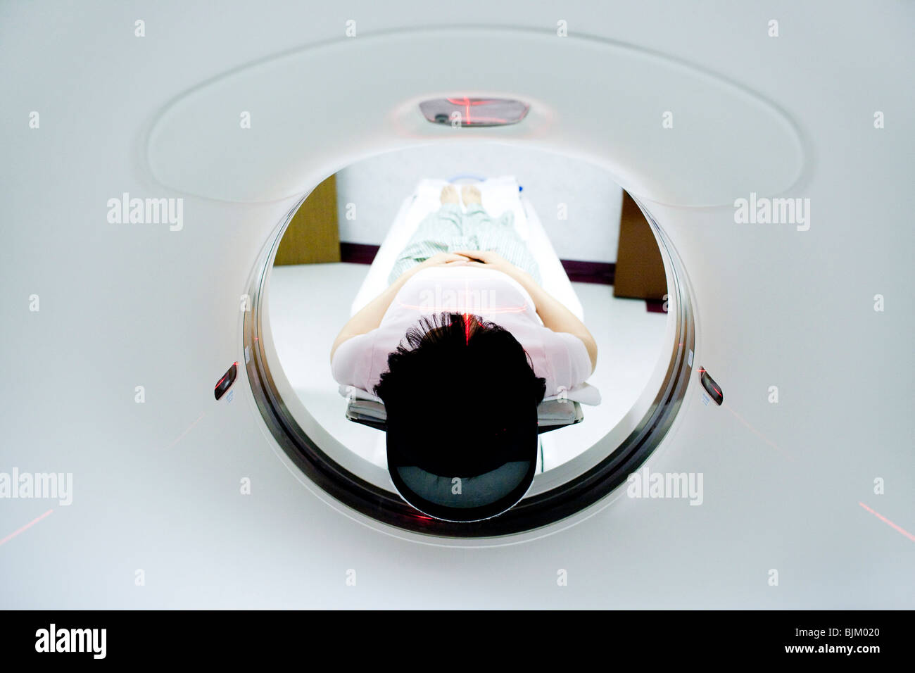Patient entering MRI machine from behind - Stock Image