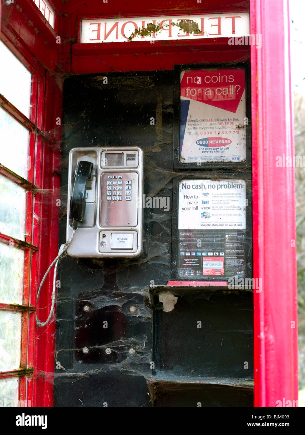 Interior of red telephone box covered in spider webs and showing little sign of recent use or cleaning - Stock Image