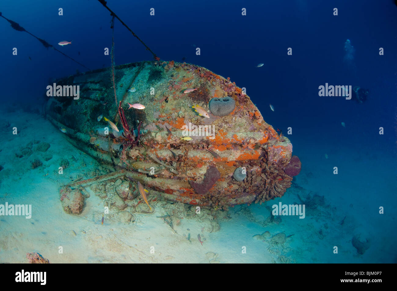 A diver views a small underwater shipwreck from afar. - Stock Image