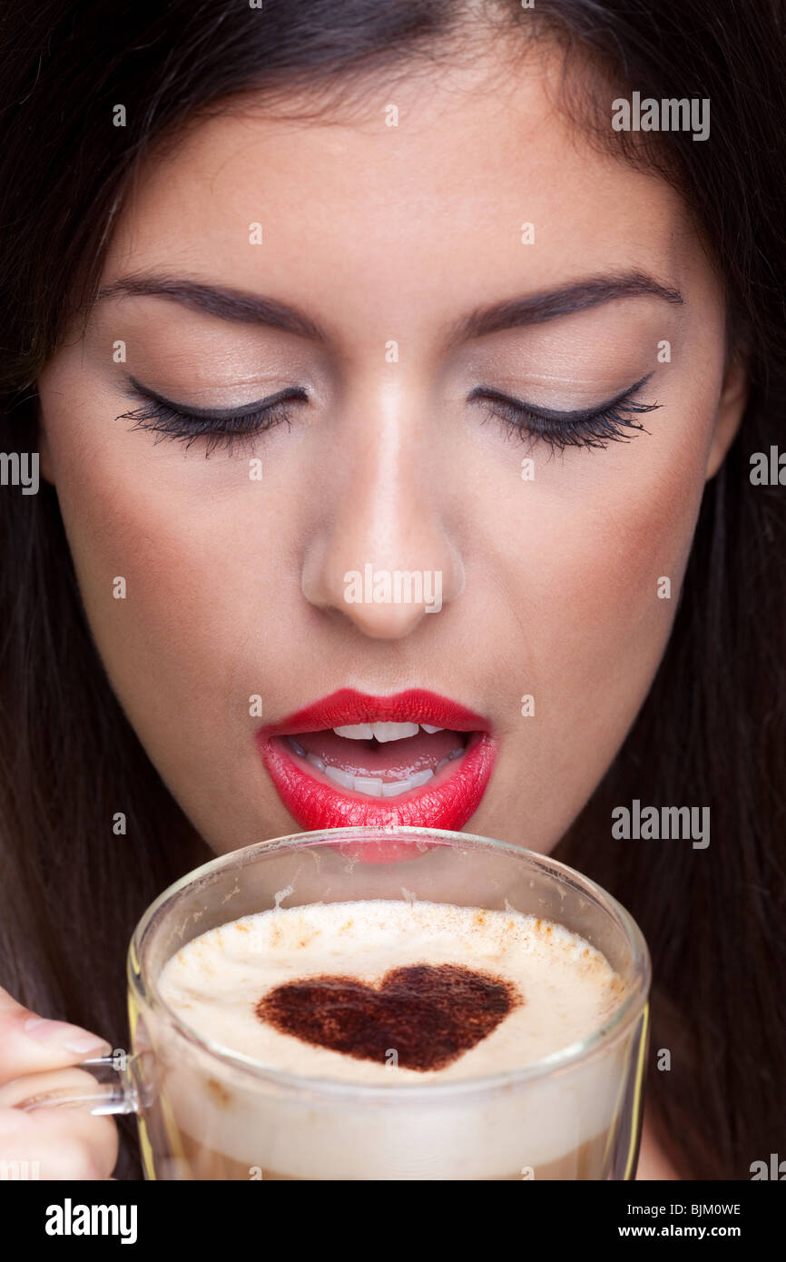 Woman drinking a cappuccino coffee with a love heart shape sprinking on top. - Stock Image