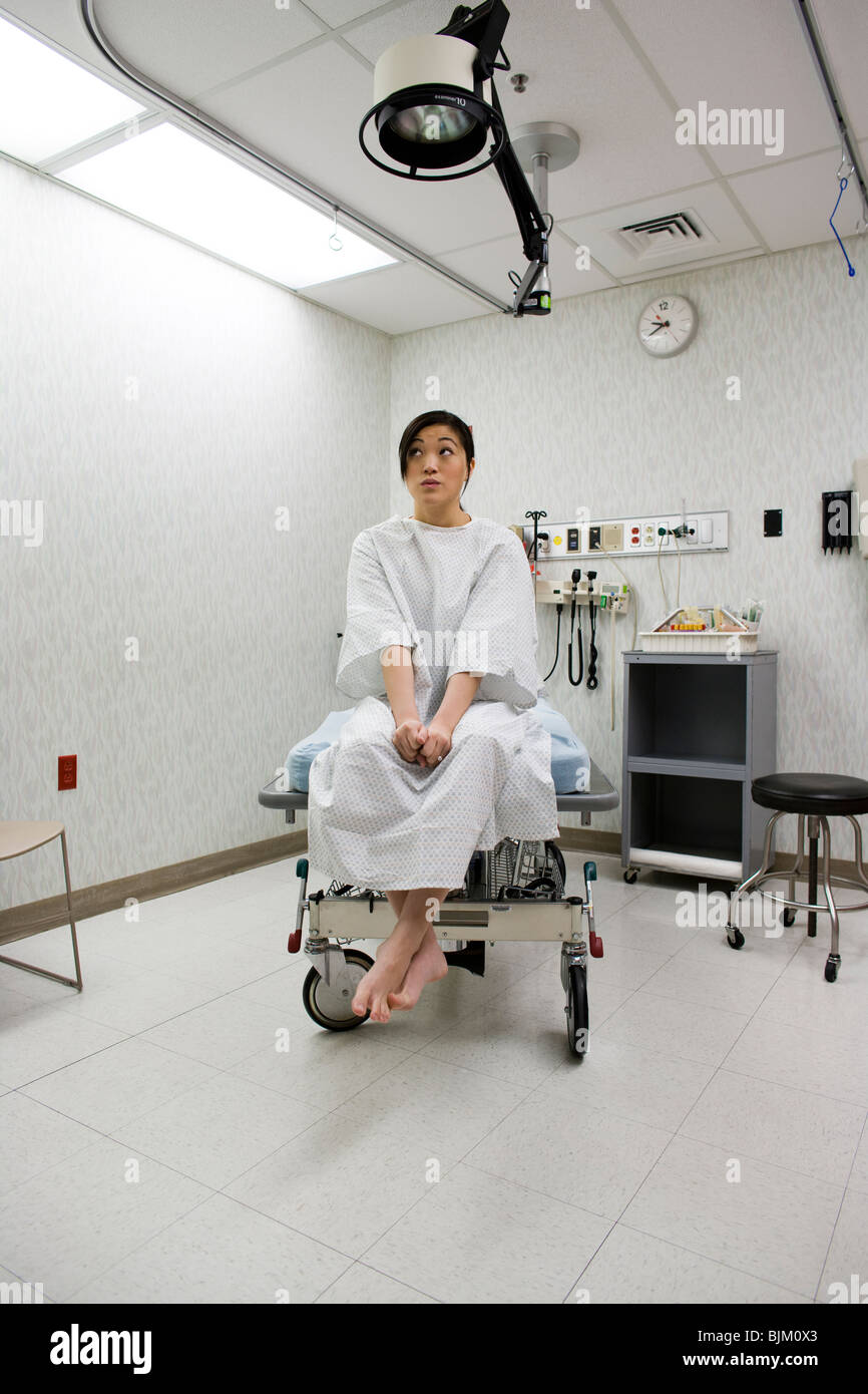 Female patient waiting anxiously in examining room - Stock Image