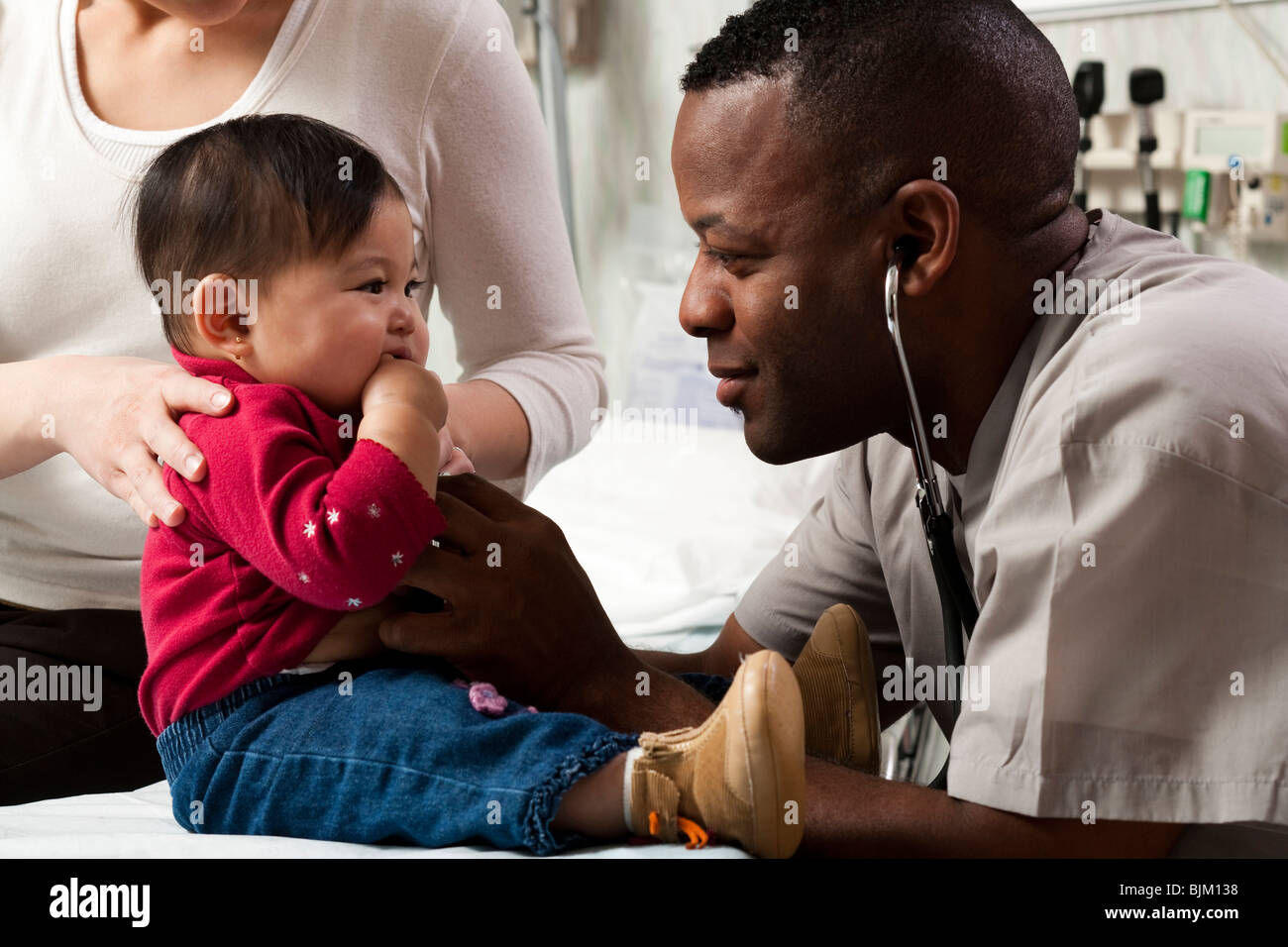 Mother and baby in examining room with doctor - Stock Image