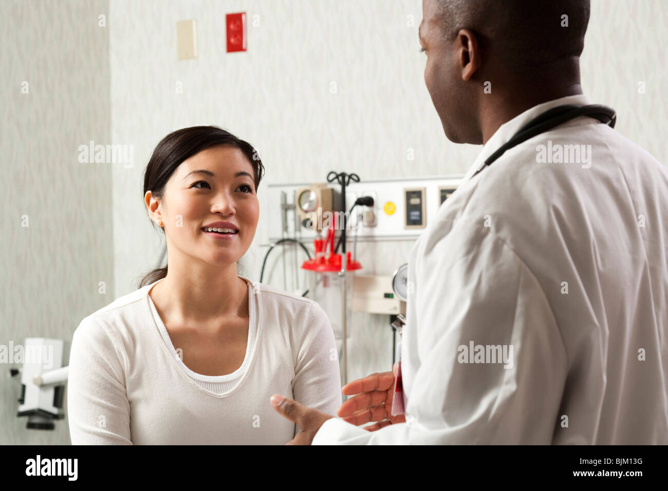 Doctor talking to woman in examining room - Stock Image