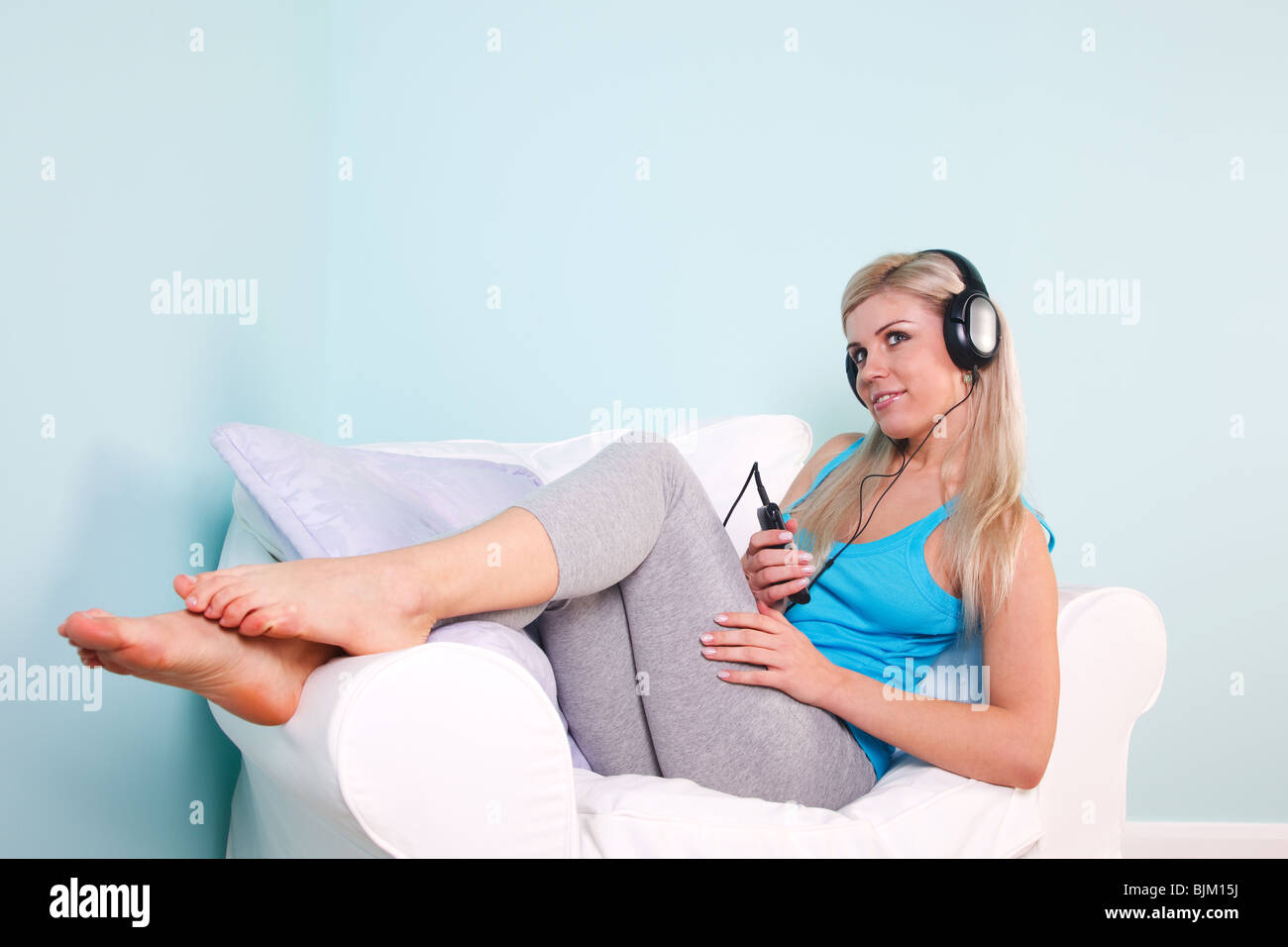 Blond woman sat in an armchair with headphones on listening to music. - Stock Image