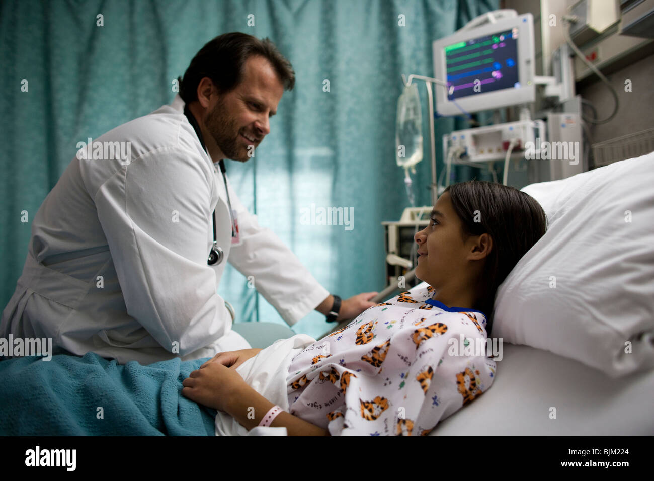 Doctor examining girl in hospital bed - Stock Image