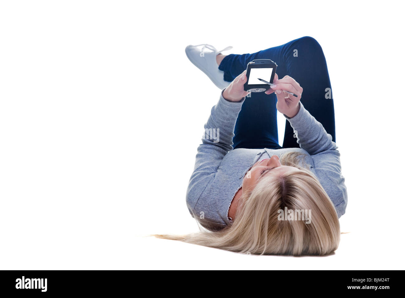 Woman lying down writing on her pda isolated on a white background, space on the screen for your own message. - Stock Image