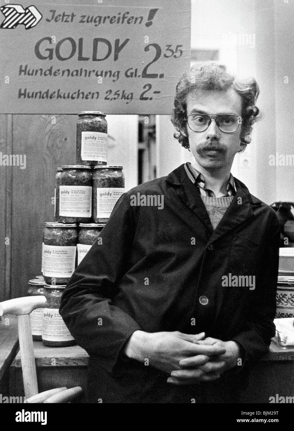 Shopkeeper and advertisement for dog food, East Germany, Europe, circa 1975 - Stock Image