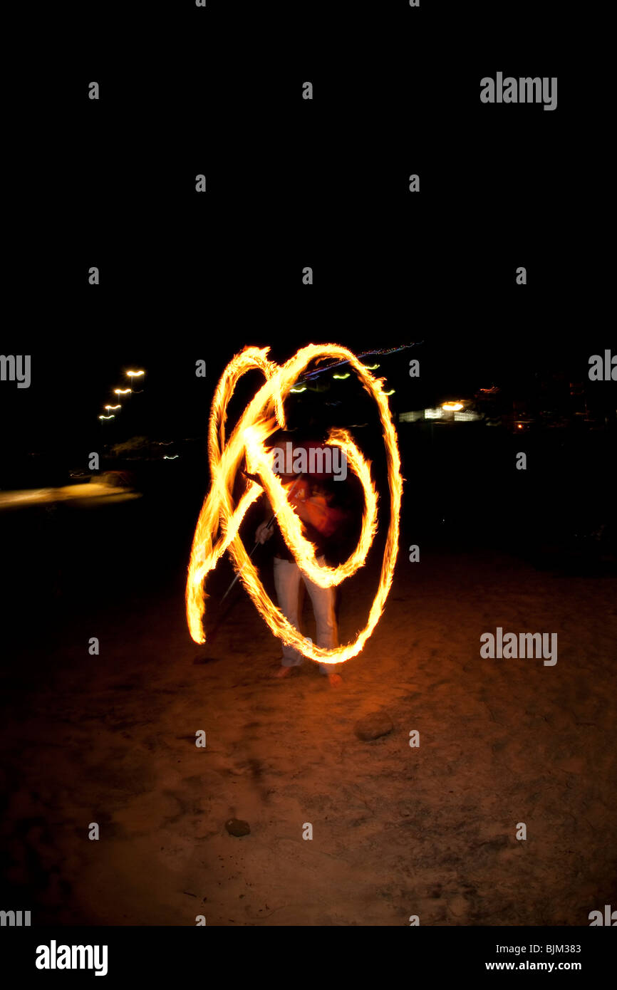 FIRE TWIRLING ON MOOLOOLABA BEACH - Stock Image