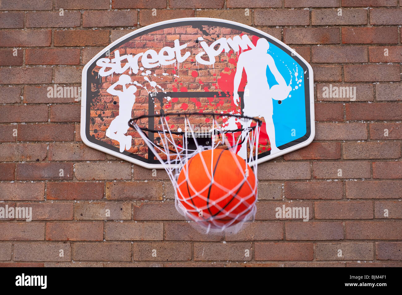 A basketball goes through the hoop net scoring a point - Stock Image