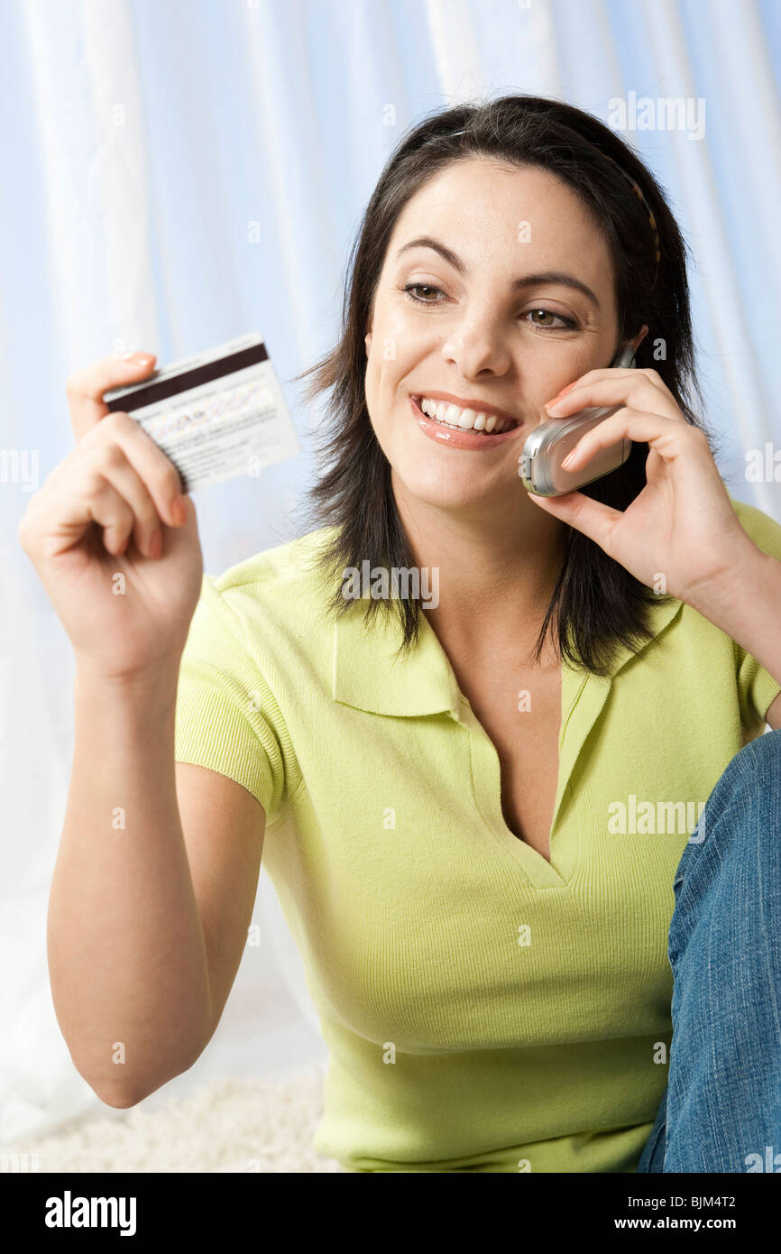 Female on cell phone with credit card - Stock Image