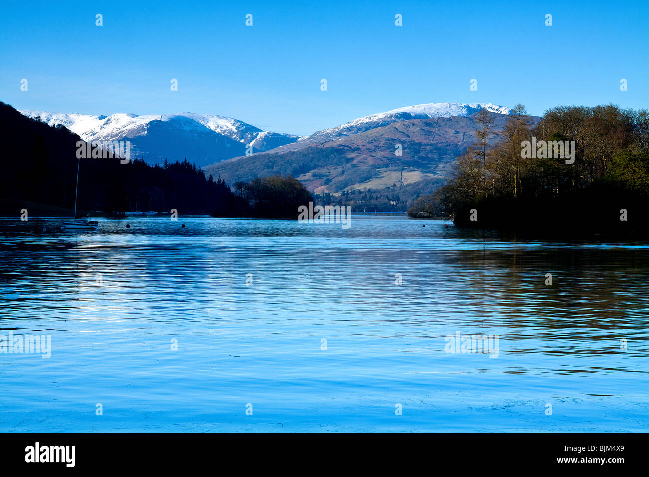 Icy Water of Lake Windermere looking North from Ferry House to snow capped mountains in early Spring. - Stock Image