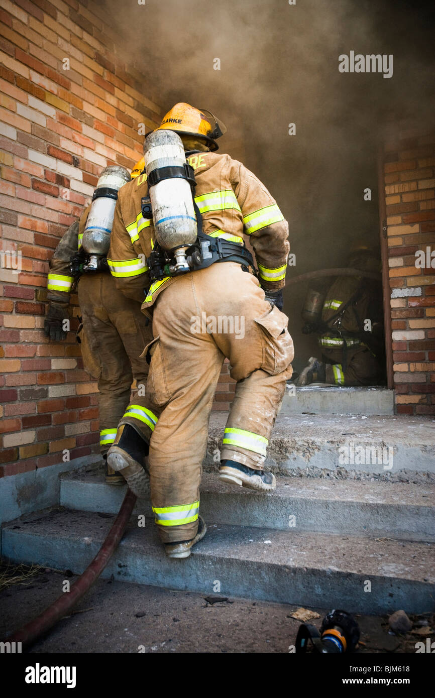 Rear View of fire fighters - Stock Image