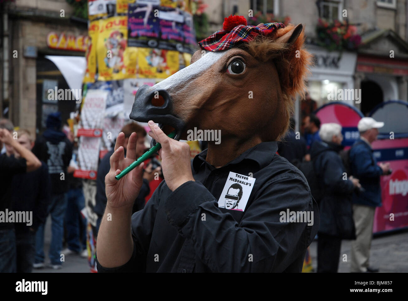 Performer with a horses head playing a penny whistle during the Edinburgh Fringe Festival in Scotland Stock Photo