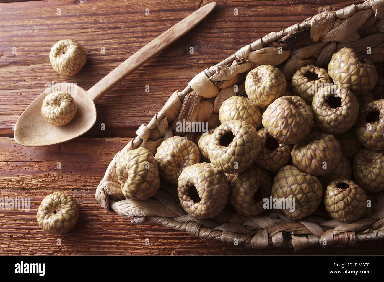 Salak or Snake Fruit (Salacca zalacca) in a wicker basket on a rustic wooden background Stock Photo