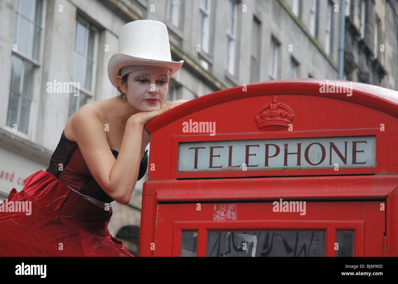 Performer on the Edinburgh Fringe Festival resting on a red telephone box on the High Street. - Stock Image