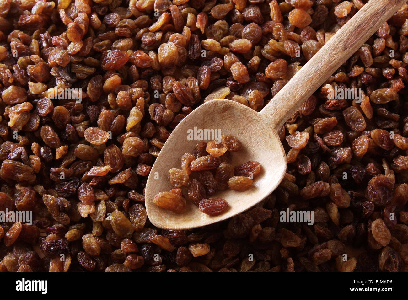 Dried raisins, sultanas, Thompson Seedless, with an old wooden spoon - Stock Image