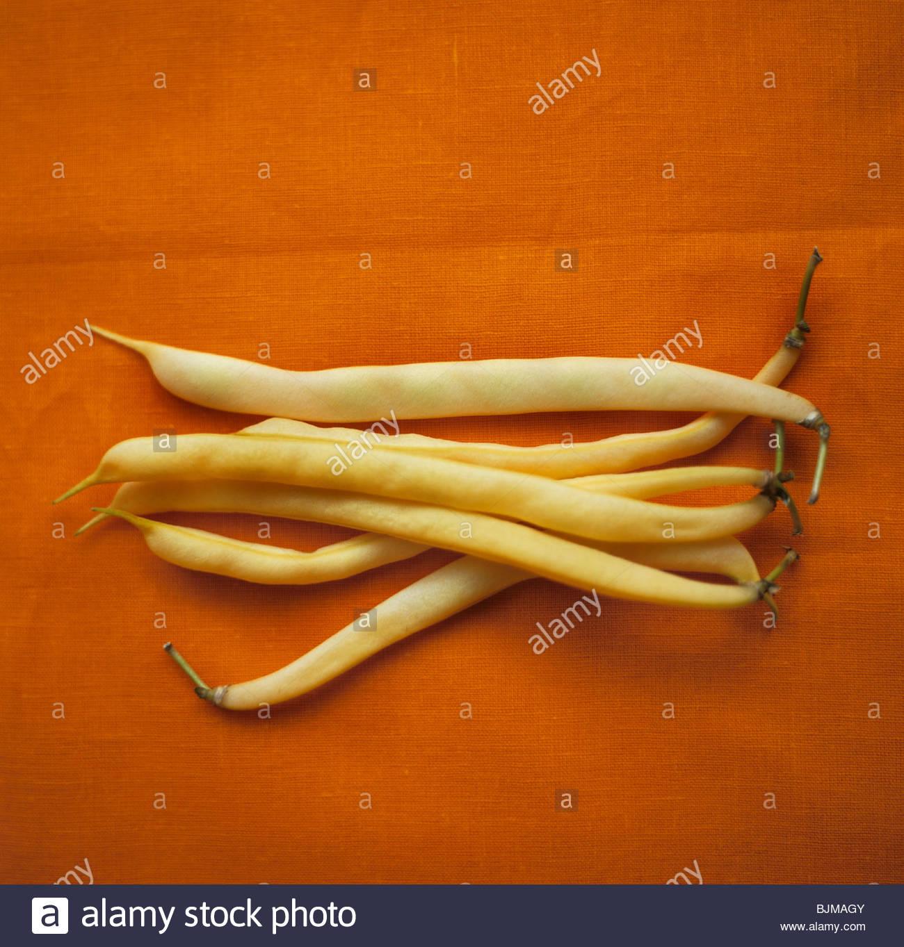 Wax beans against orange background - Stock Image