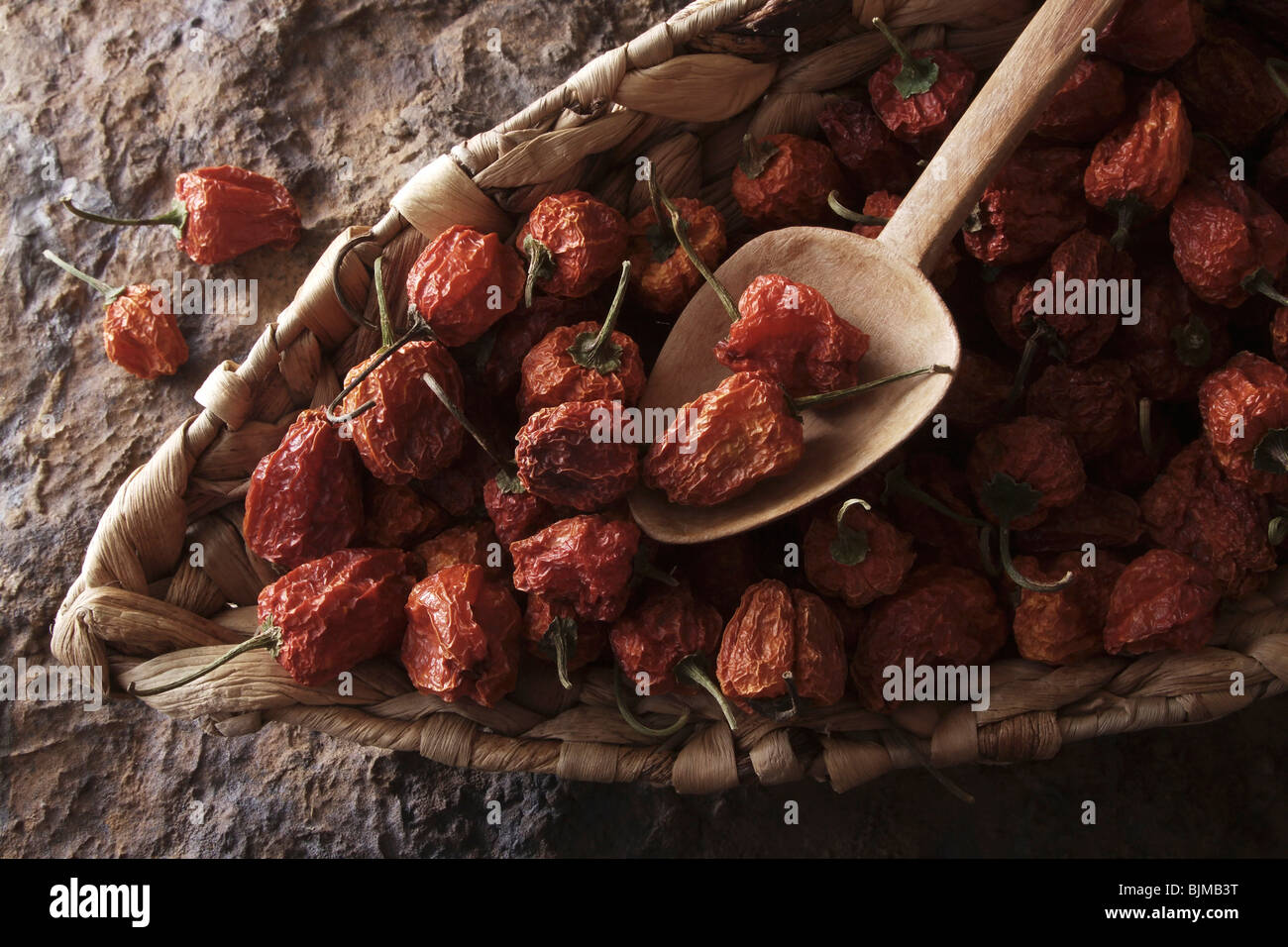 Mini-Peppers (Capsicum) with a wooden spoon in a wicker basket on a stone surface - Stock Image