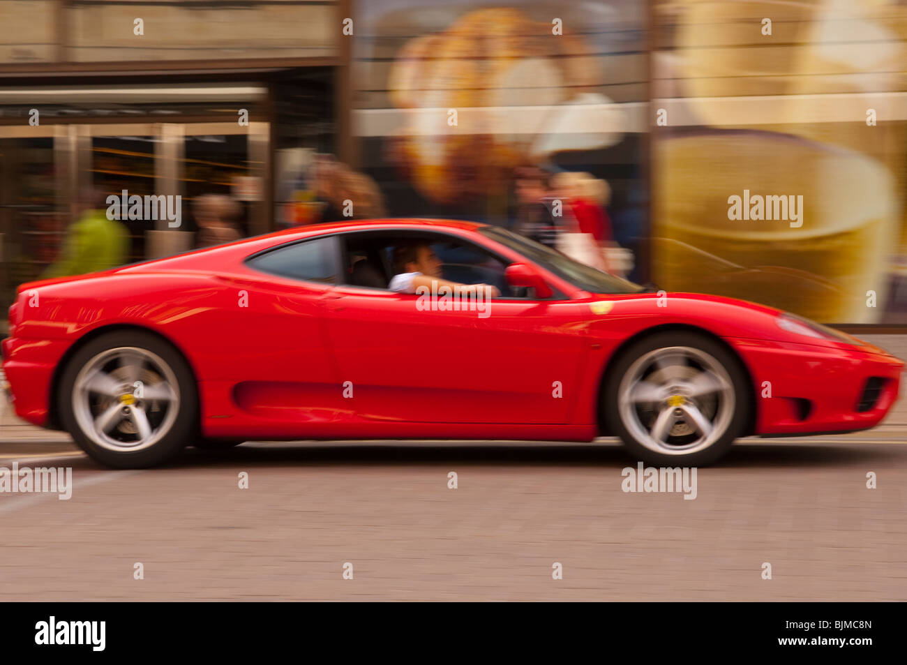 A red ferrari drives through the city showing movement with intentional blur in Norwich , Norfolk , England , Britain Stock Photo