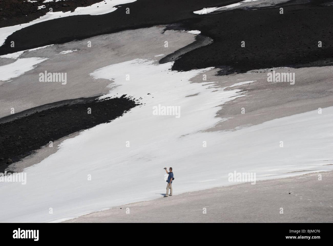 Italien, Sizilien, Ätna schwarze Lava und Schnee, einzelner Tourist Italy, Sicily, Mount Etna, black lava and - Stock Image