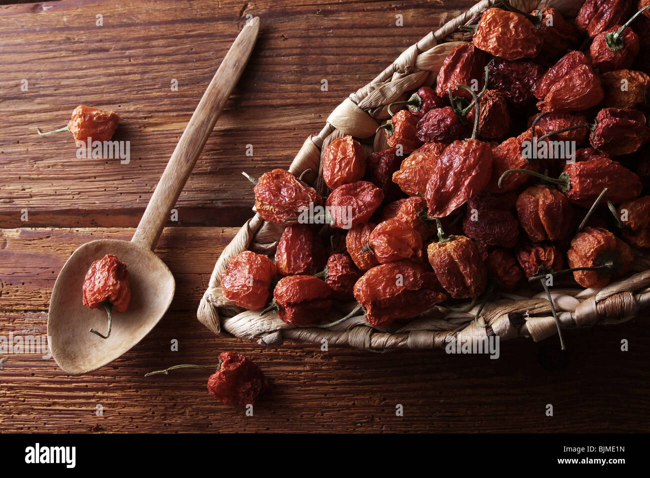 Mini-Peppers (capsicum) in a wicker basket on a rustic wooden background - Stock Image