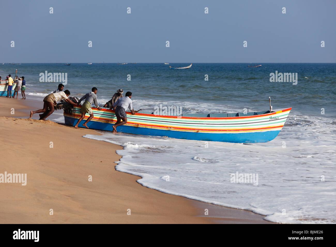 Fishermen pushing their fishing boat into the sea, Somatheeram Beach, Malabarian Coast, Malabar, Kerala state, India, - Stock Image
