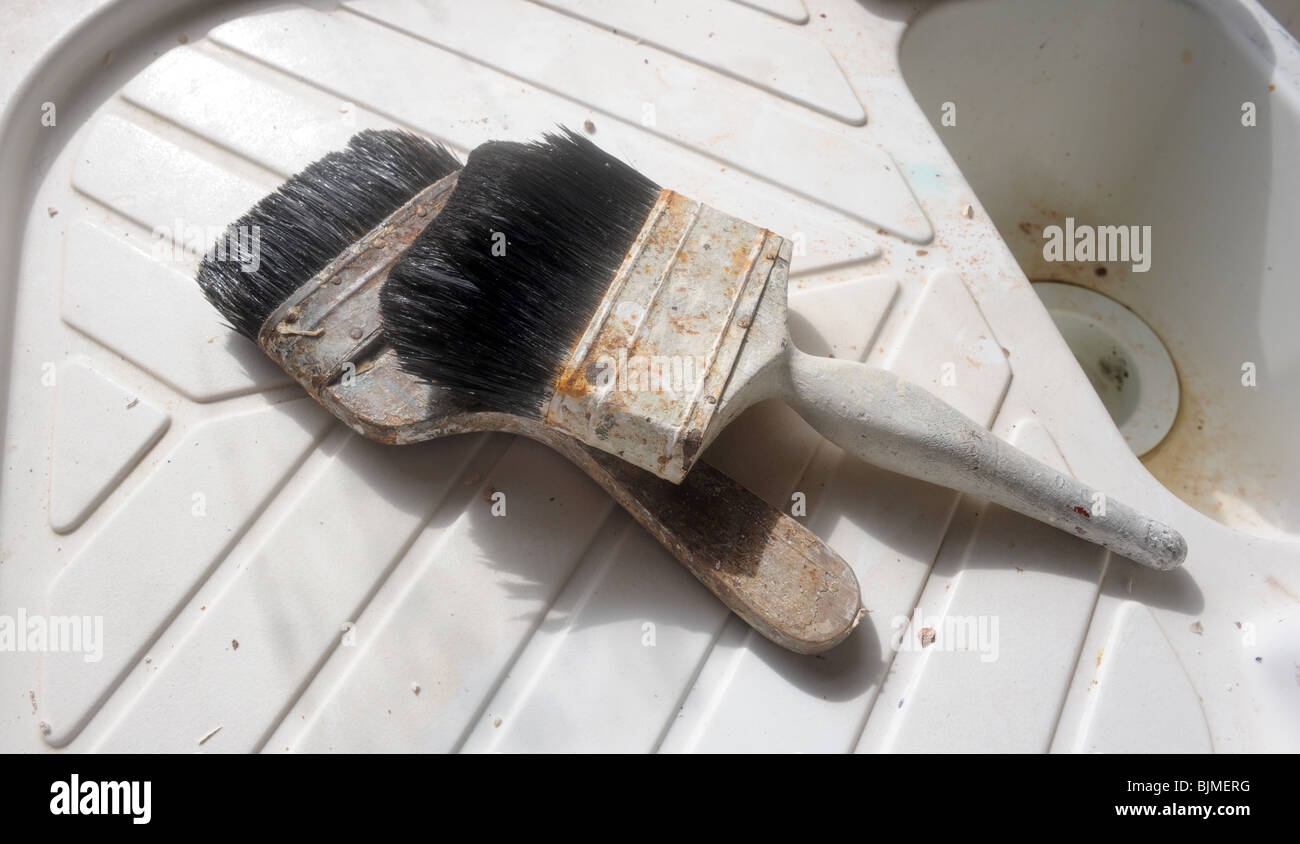A PAIR OF PAINT BRUSHES ON A SINK UNIT,UK - Stock Image